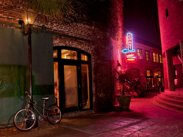 A bicycle rests against a lamp post in the Coast Bar & Grill alley.