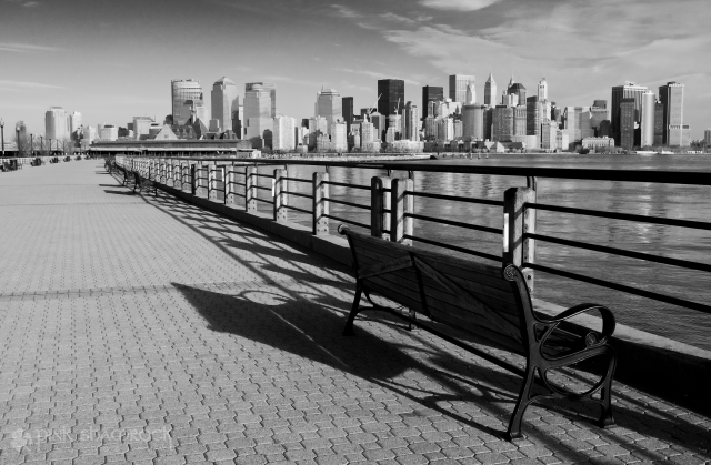 A bench sits empty in Liberty State Park, overlooking the Hudson River and the NYC skyline.