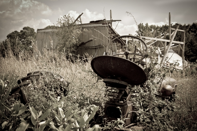 An old, overgrown tractor overlooks a dilapidated barn in upstate NY.